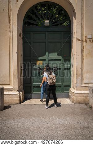 Two Young Women Near The Famous Keyhole Of The Gardens Of Order Of Malta On Aventine Hill In Rome, I