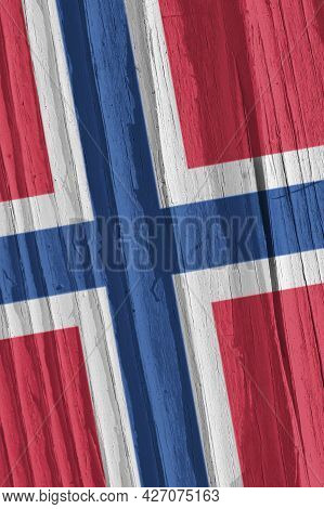 The Flag Of Norway On A Dry Wooden Surface, Cracked With Age. It Seems To Flutter In The Wind. Verti