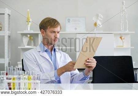 Young Brazilian Scientist Read The Results Of Chemical Compound Research On The Clipboard. Working A