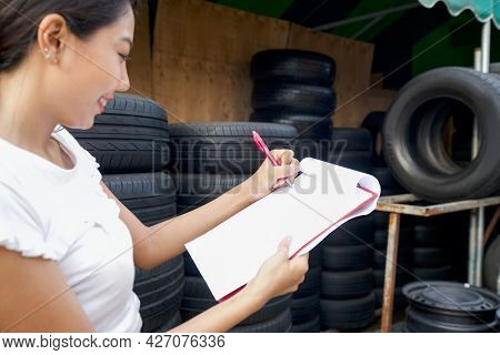Red Pen, Paper And Clipboard In Owner Of The Auto Parts Store Hand. Several Car Tires Are Lined Up I