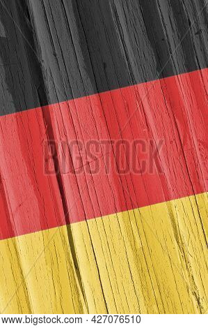The Flag Of Germany On Dry Cracked Wooden Surface. It Seems To Flutter In The Wind. Vertical Backgro