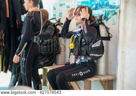 Anapa, Russia - June 20, 2019: Child Girl Puts On A Wetsuit And Prepares To Dive. Girl Scuba Diver