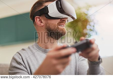Low Angle Of Content Bearded Male Gamer In Vr Goggles And With Controller Playing Videogame While Sp