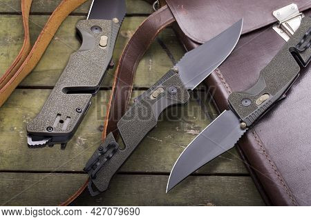 The Knife Is Shown In Three Angles. Folding Military Knife. Knife And Military Tablet.