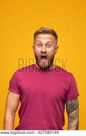 Overwhelmed Adult Bearded Hipster Guy With Tattoo On Arm Screaming Loudly And Looking At Camera Whil