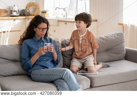 Indifferent Young Mother Surfing Social Media Addict Irritated With Disturbing Little Son. Mom Focus