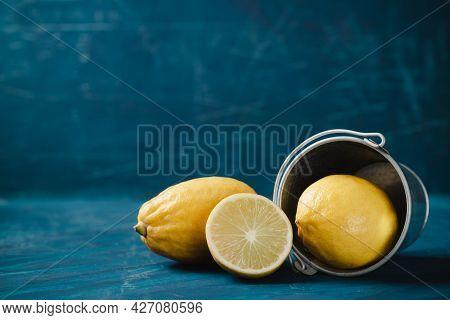 Fresh Lemon With Bucket On Dark Green Color Background