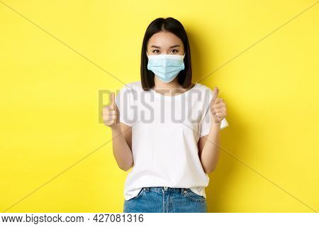Covid-19, Quarantine And Social Distancing Concept. Cheerful Asian Woman In Medical Mask And White T