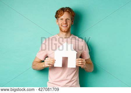 Real Estate Concept. Young Man With Red Hair, Wearing T-shirt, Showing Paper House Cutout And Smilin