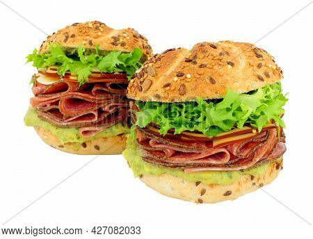 German Style Salami And Cheese Filled Sandwich Rolls With Fresh Lettuce And Guacamole Isolated On A