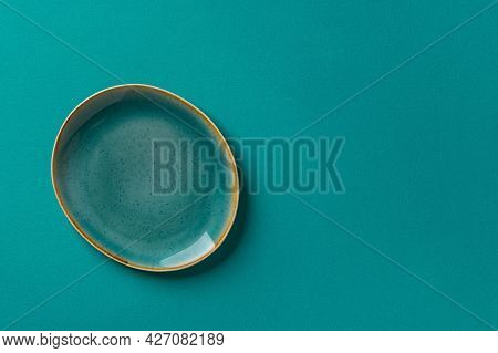 Oval Turquoise Blue Ceramic Plate With Brown Border Over Textured Teal Background. Modern Empty Dish