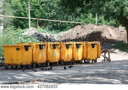 Social Problems, Waste Recycling, Yellow Plastic Dirty Garbage Cans For Household Waste Stand In A R