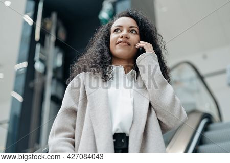 Young Woman Talking On Her Smartphone Standing On The Escalator Steps .