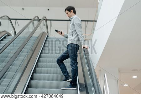Young Man With A Smartphone Waiting For Someone Standing Near The Escalator.