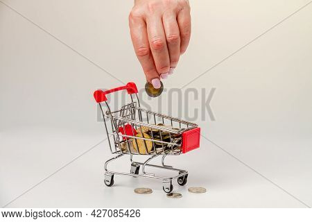 A Woman's Hand Puts 10 Israeli Shekels Into A Grocery Cart With Israeli Coins