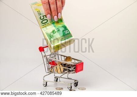 A Woman's Hand Puts A Stack Of 50 Israeli Shekels Into A Grocery Cart Filled With Israeli Coins.