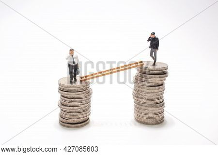 Mini People Walking From Low To High Pile Of Coins.