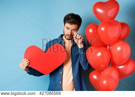 Sad And Heartbroken Man Crying, Wiping Tears, Standing With Red Heart And Balloons, Breakup On Valen