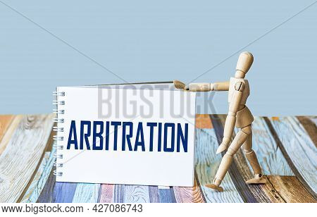 The Word Arbitration Is Written On A Notebook, Next To A Wooden Doll On A Light Background.