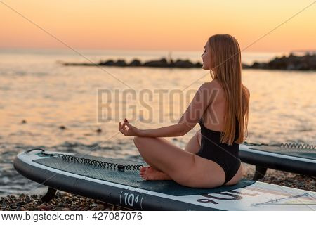 Yoga Sup Board. Beautiful Woman Meditates On A Surf Board. In The Background, The Ocean, The Horizon