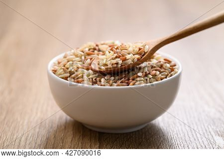 Organic Thai Highland Brown Rice Grain In A Spoon And Bowl On Wooden Table (cargo Rice, Loonzain Ric