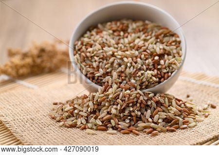 Organic Thai Highland Brown Rice Grain In A Bowl And Pouring (cargo Rice, Loonzain Rice Or Husked Ri