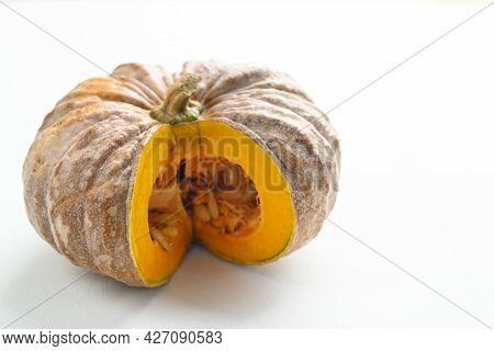 Close Up Of Cutting Organic Pumpkin On White Background