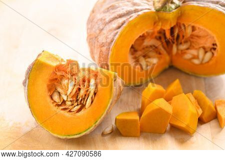 Close Up Of Cutting Organic Pumpkin On Wooden Background