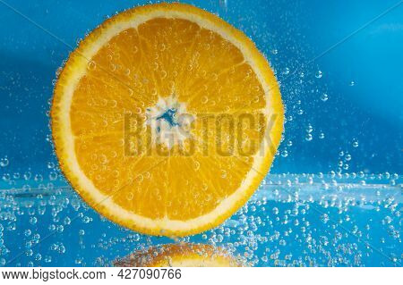 Orange Fruit In Water Close Up, Under Water With Bubbles.