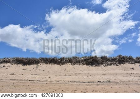 Beautiful Fluffy White Clouds Over A Beach On Cape Cod.