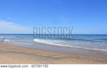 Gentle Waves Lapping The Beach Along The Coast Of Cape Cod.