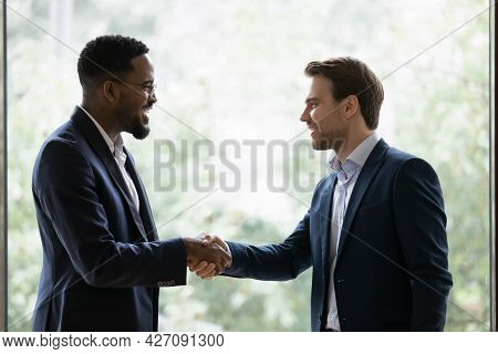 Two Diverse Businessmen, Business Partners Shaking Hands At Window