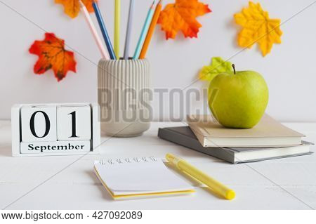 Back To School Concept. Open Notepad With Pen, Notebooks, Pencils And Green Apple And Calendar Dated