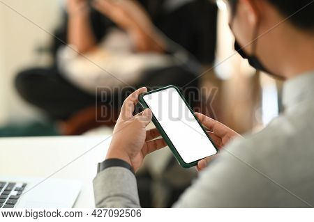 Cropped Shot Of Man Hands Holding Mock Up Smartphone Blank Screen While Sitting In Meeting Room.