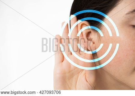 Hearing Test. A Young Woman Holds Her Hand To Her Ear, Close-up. Isolated On A White Background. Cop