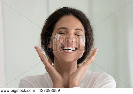 Overjoyed Millennial Latina Woman Feel Pleasure Applying Cream On Face
