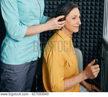 Hearing Test To Mature Woman. Senior Woman During Hearing Test And Audiometry At Hearing Clinic With