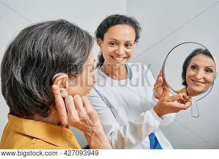 Mature Woman With Bte Hearing Aid Looks At Himself In Mirror Held By Smiling Audiologist, And Tries