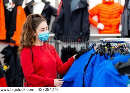 Consumerism. Portrait Of A Young Woman In A Medical Mask Choosing Clothes In A Store. The Concept Of