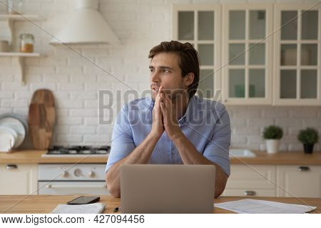 Young Male Studying At Kitchen Pondering Distracted From Laptop Screen