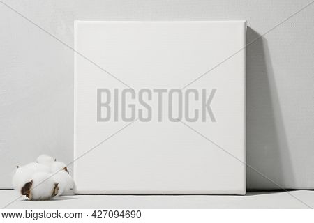 Blank Canvas And Fluffy Cotton Ball Against Grey Wall. Mockup Poster. White Canvas, Gallery Wrap.