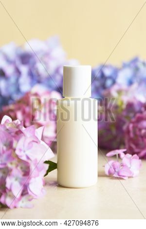 Cosmetic Bottle And Hydrangea Flowers On Background. Body And Skin Care Concept