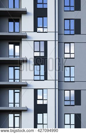 A Part Of Modern Residential Building Facade With Reflection Of Cloudy Blue Sky In Windows
