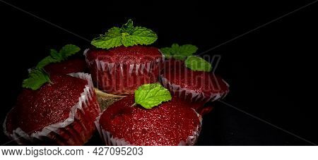 Closeup Of Delicious Red Velvet Cupcakes Or Muffins Decorated With Mint On Top In A Isolated Black R