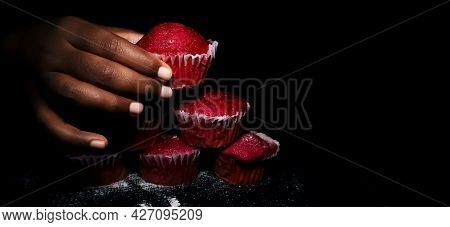 Closeup Of Hand Holding Delicious Red Velvet Cupcakes Or Muffins In A Isolated Black Rustic Backgrou