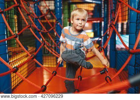 Happy Boy Playing In Indoor Playground On Net Trail. Child Having Fun On Modern Playground. Cute Kid