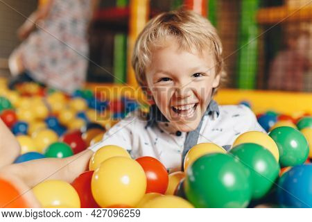Happy Little Kid Boy Playing At Balls Pool Playground. Happy Kid Playing In Pool With Plastic Multic
