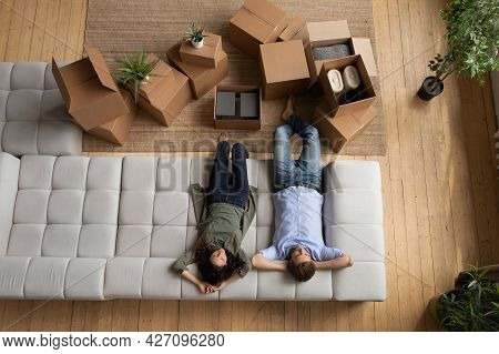 Young Married Couple Rest On Cozy Couch After Packing Stuff