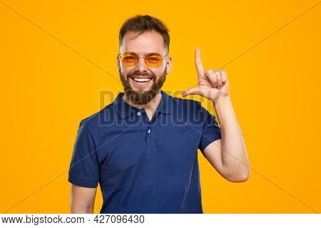 Optimistic Adult Bearded Guy In Casual Shirt And Trendy Yellow Sunglasses Looking At Camera And Poin