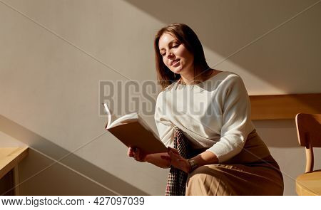 Happy Relaxed Young Female With Book Sitting Near Table In Cafe And Enjoying Interesting Novel